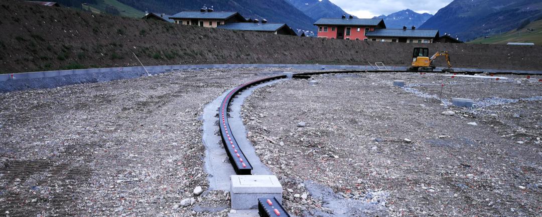Lavori in corso: si nota la creazione del vallo all'esterno della pista e la posa delle canaline di raccolta delle acque.