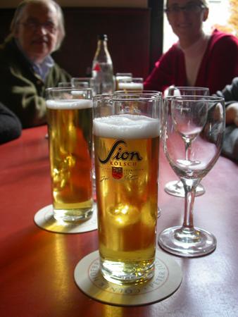 Bicchieri di Kölsch Sion in un locale di Colonia: in questa foto, sullo sfondo, Pietro Chianchiano, il fondatore di Tsport (scomparso nel 2017), con una nostra giornalista.