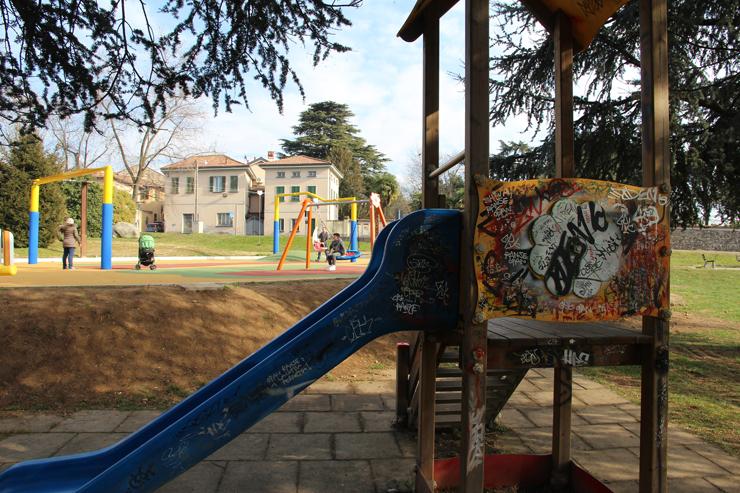 Sullo sfondo del nuovo parco giochi, una delle vecchie installazioni, ricoperta di scritte e graffiti.